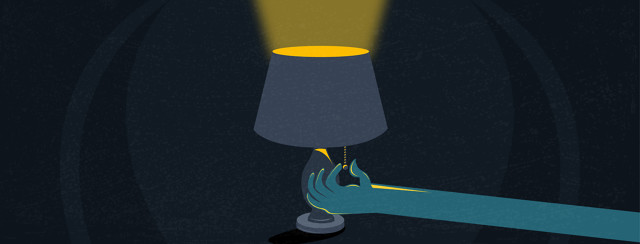 A lamp is illuminating a dark room, as an arm extends from the side to pull the cord to turn it off.