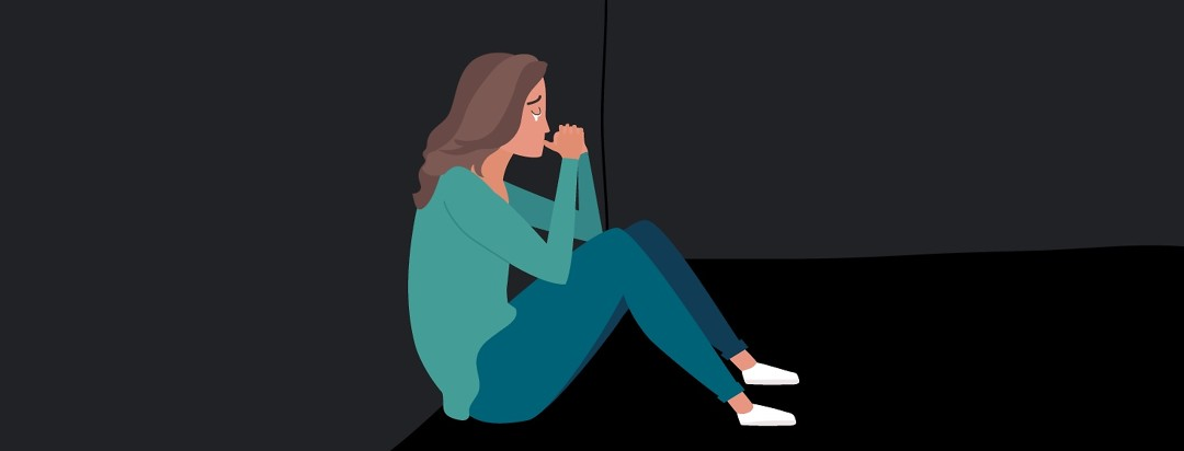 A woman sits in the dark crying
