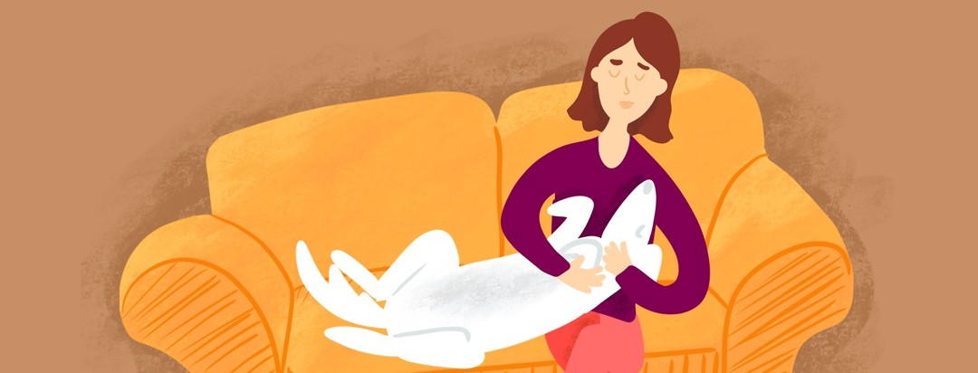 A woman cuddles her dog in her lap on the couch