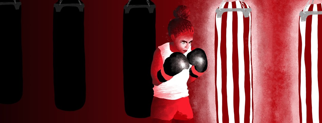 A woman in boxing gloves looking determined at a highlighted pair of punching bags