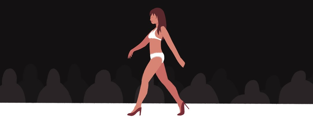 A woman proudly walks the catwalk in lingerie