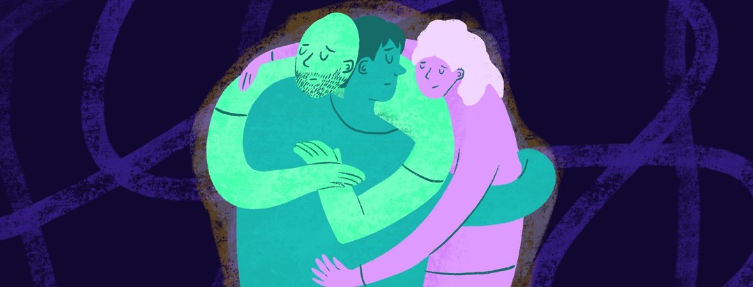 Three people hug each other in a supportive way