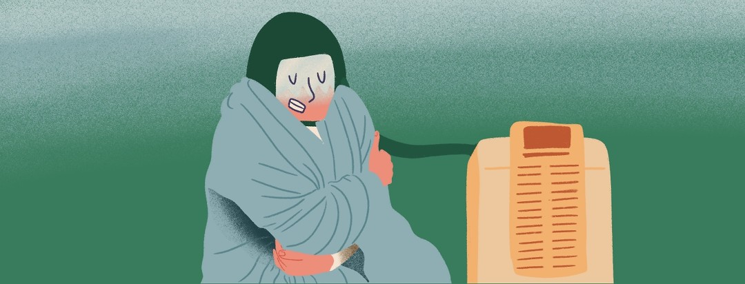 Person shivers under a blanket while wearing a cold cap attached to a machine