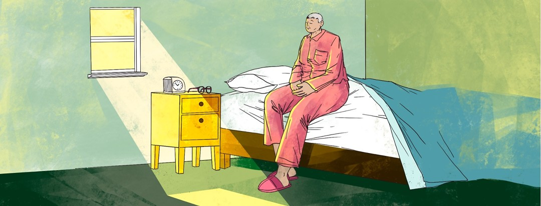 An older woman sits up in bed peacefully in the morning, with her eyes closed