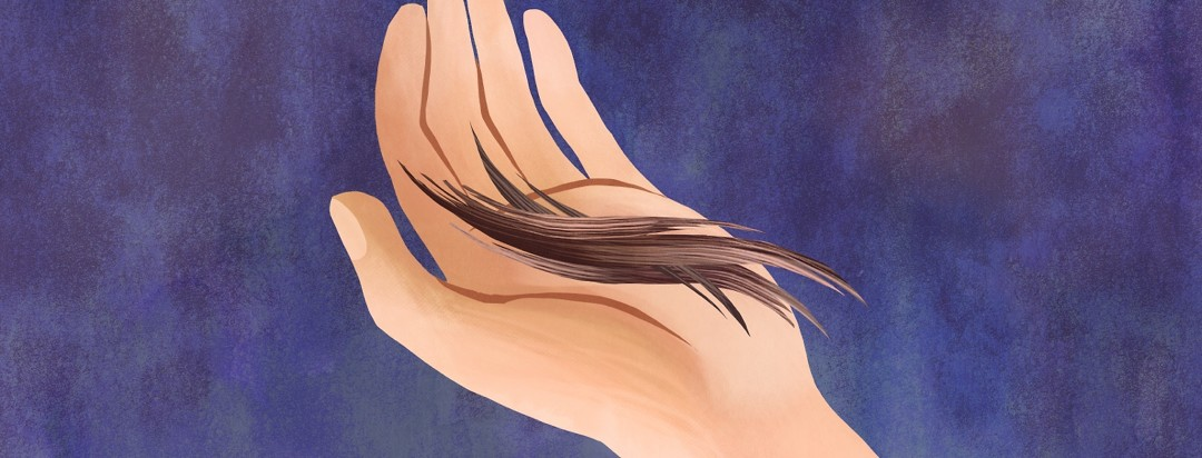 Close-up of a person holding pieces of hair in their hand