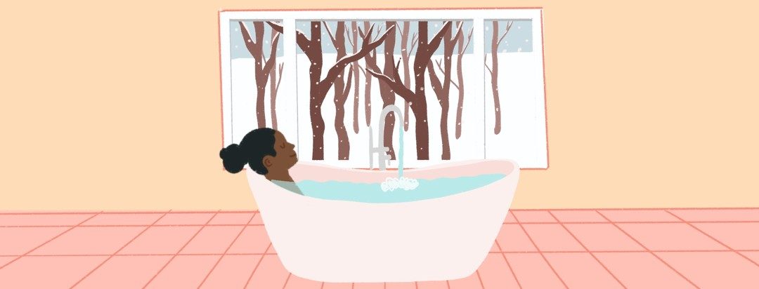 A woman relaxes in the bath while outside of her window shows a snowy scene