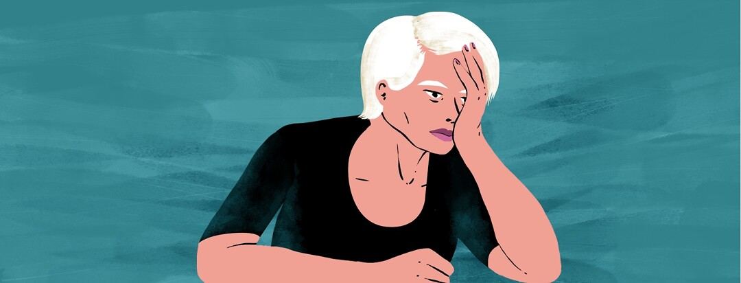 An older woman sits at a table with her head in her hand. She looks impatient, irritated, and weary