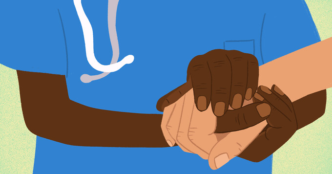 A nurse or doctor holds the hand of a patient